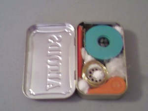 This is the tin, packed with all the odd shaped objects, filling the deeper half of the tin to capacity.